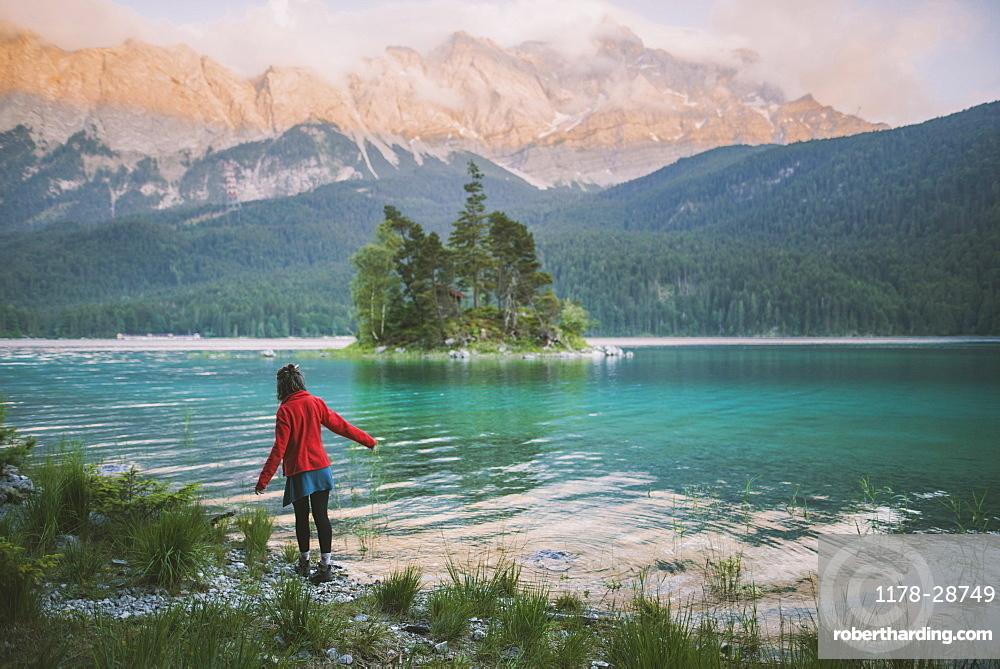 Germany, Bavaria, Eibsee, Young woman walking at shore of Eibsee lake in Bavarian Alps