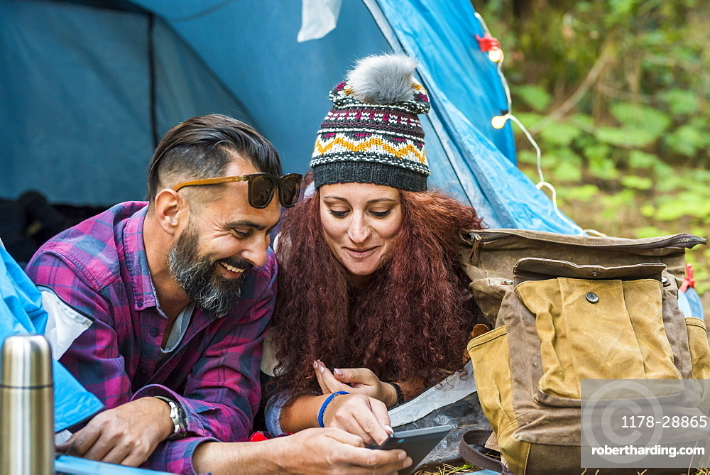 Smiling couple lying in tent using tablet