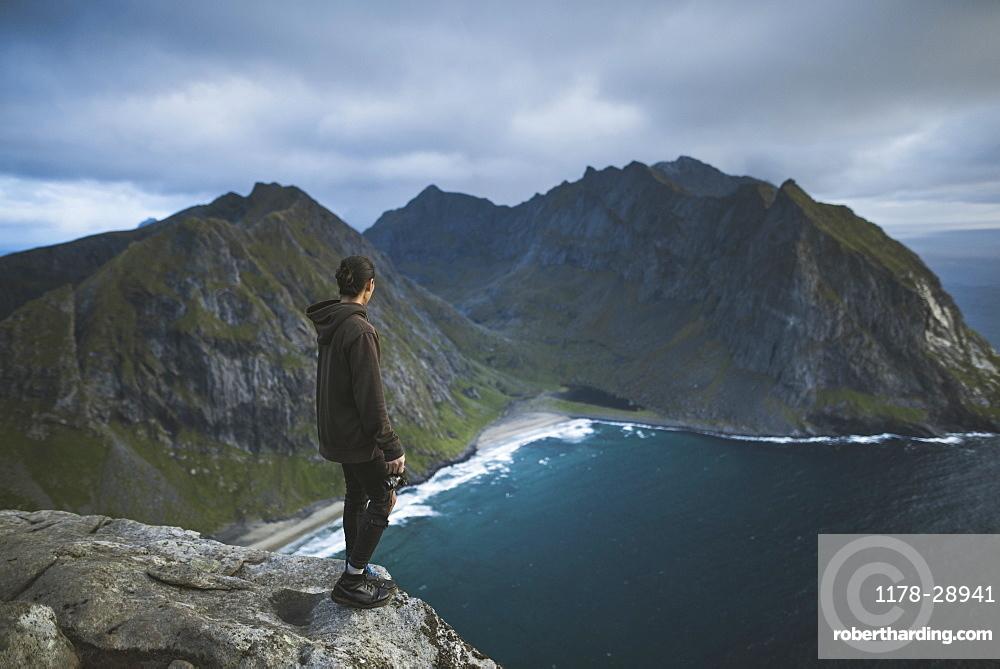 Man holding camera on cliff at Ryten mountain in Lofoten Islands, Norway