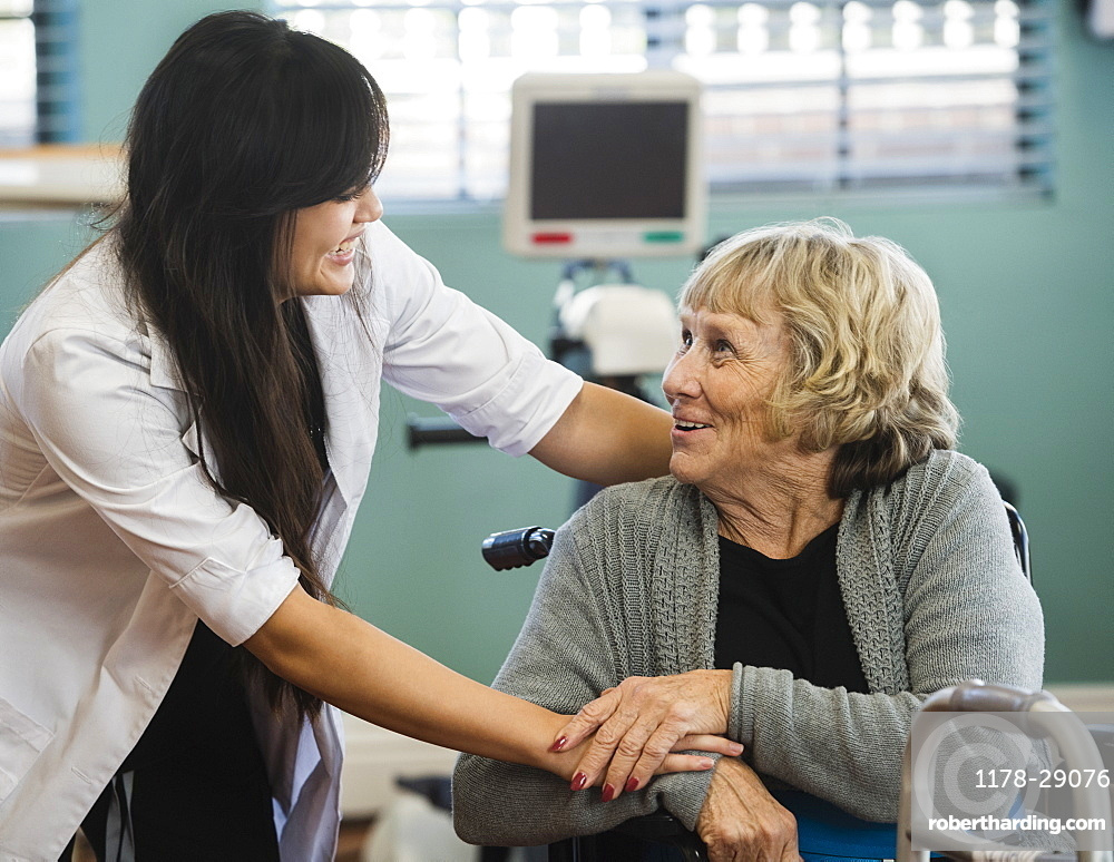 Smiling doctor and senior woman holding hands at rehabilitation center