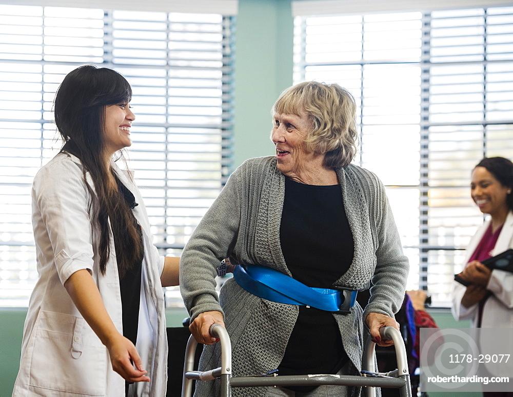 Smiling doctor helping senior woman use walking frame