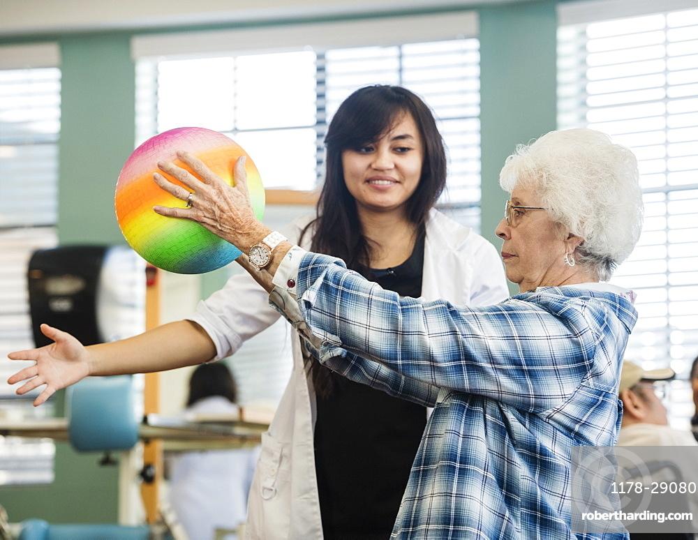Senior woman holding ball at rehabilitation center
