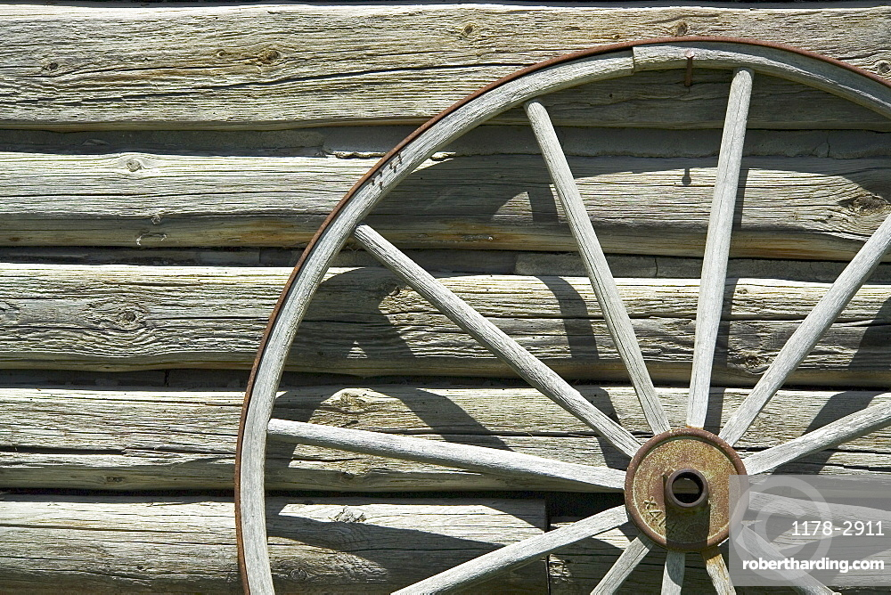 Wagon wheel against wooden wall