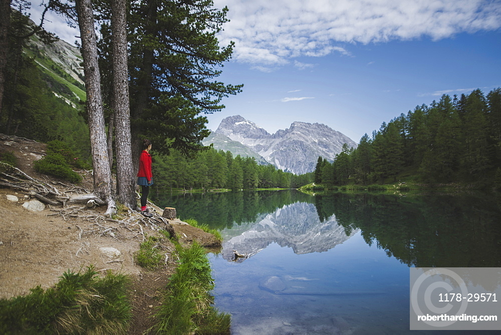 Switzerland, Bravuogn, Palpuognasee, Young woman resting on bench nearPalpuognaseelake in Swiss Alps