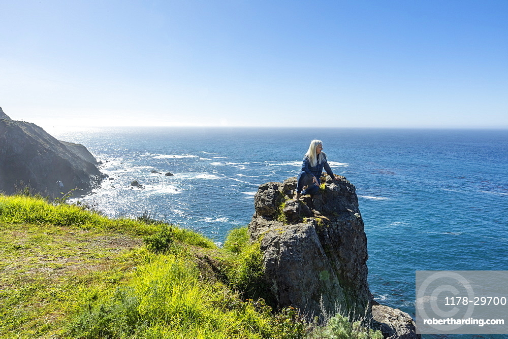 USA, California, Big Sur, Senior woman sitting at the edge of cliff watching view