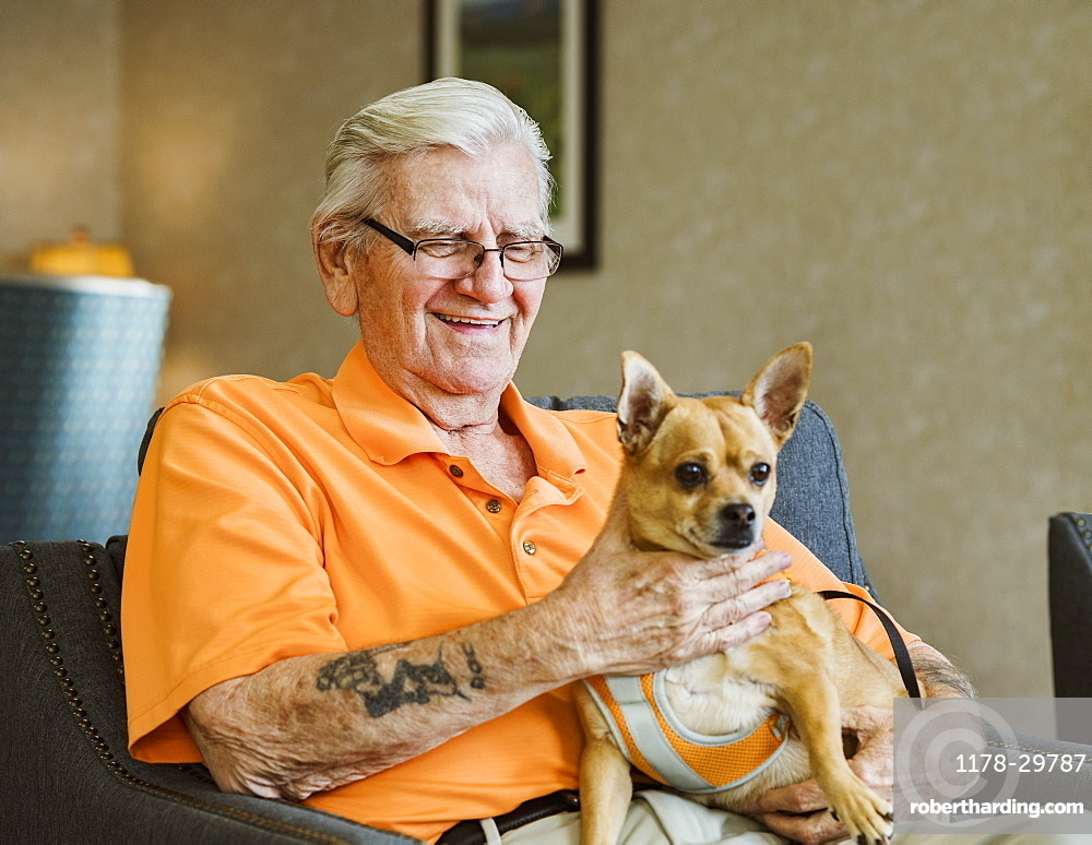 Senior man holding service dog