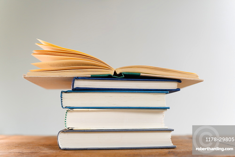 Open book on top of stack of books on desk