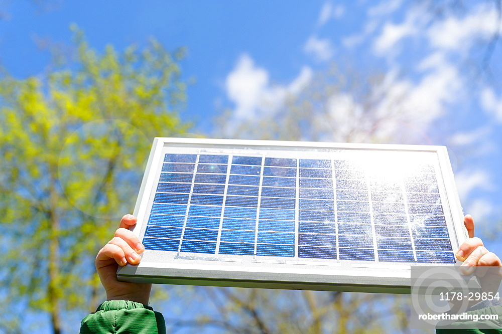Close-up of boys (4-5) hands holding solar panel against sky