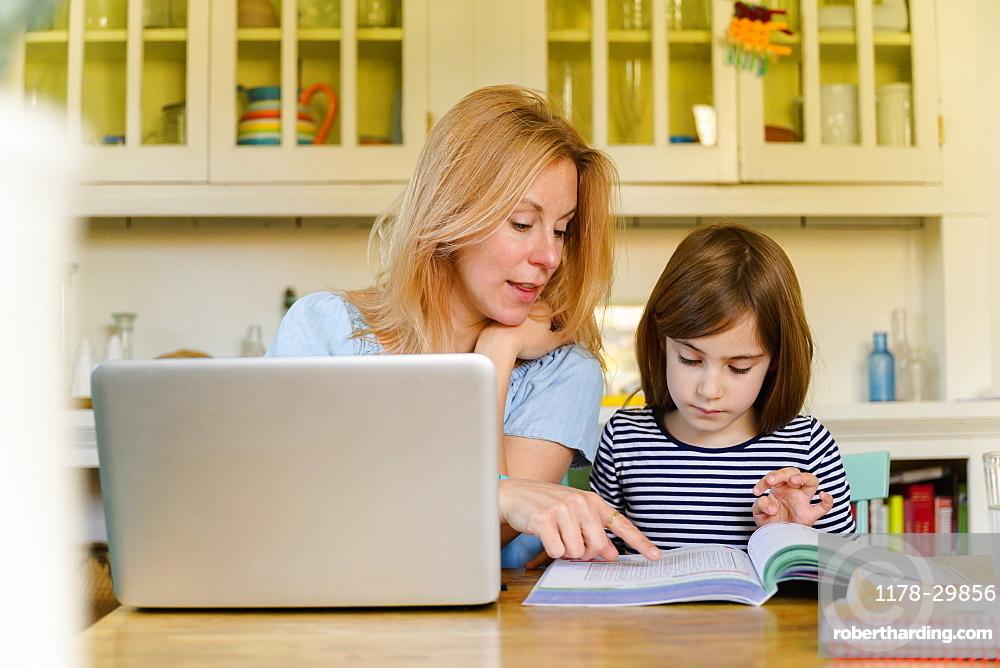 Mother helping daughter (6-7) doing homework