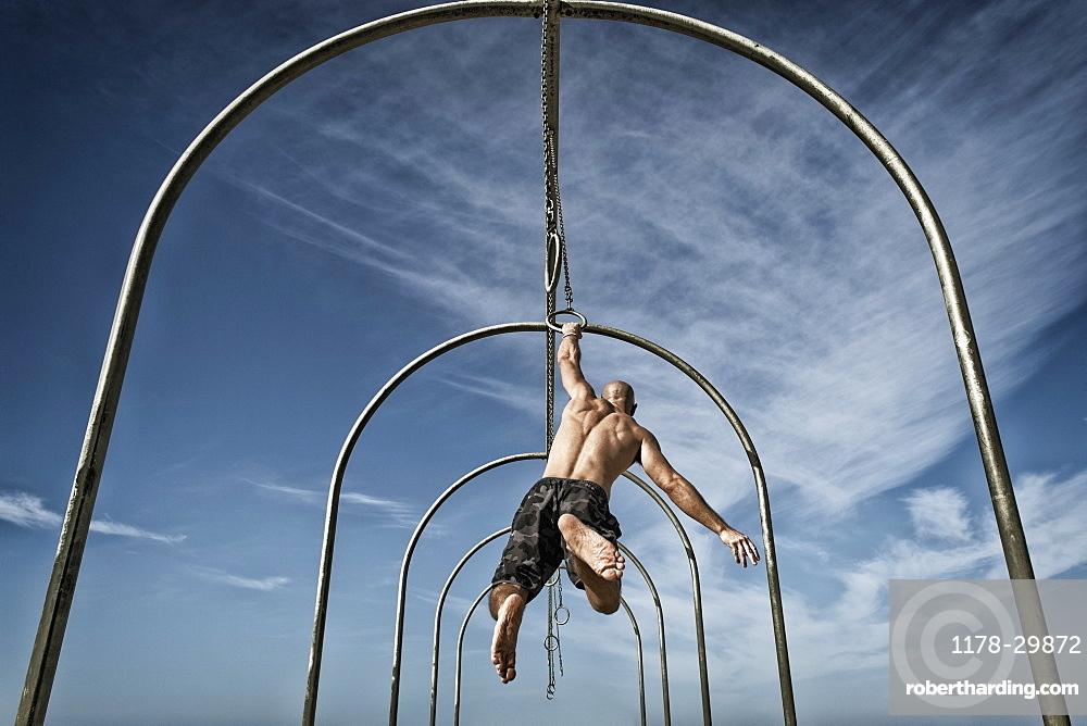 Man exercising on gymnastics rings