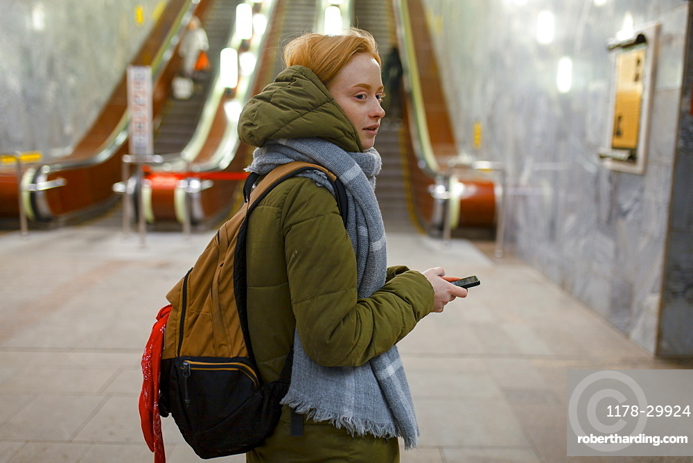 Russia, Novosibirsk, Young woman standing by escalator in subway