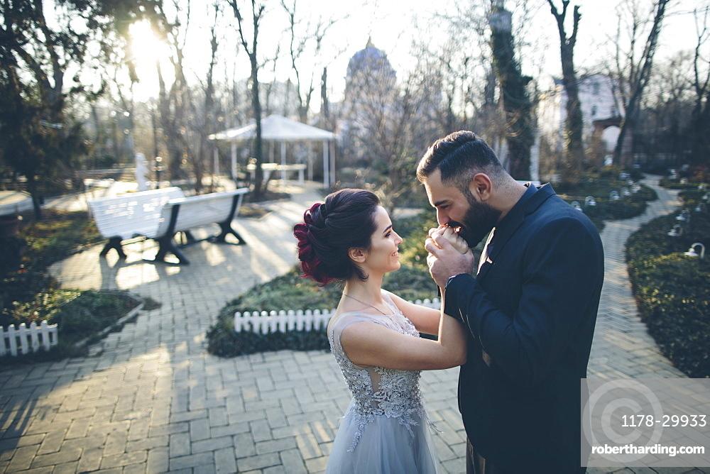 Groom kissing hands of his newlywed wife in garden