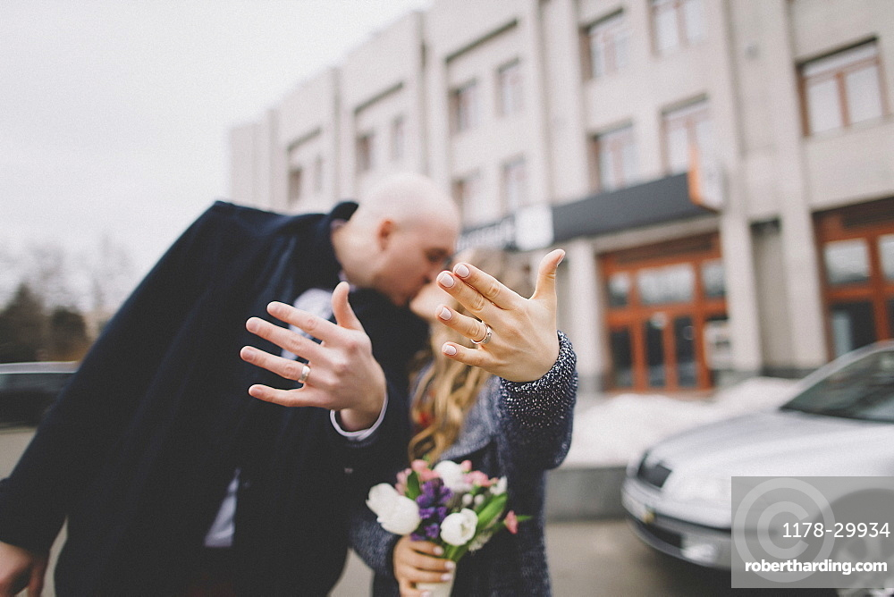 Newlywed couple kissing on street