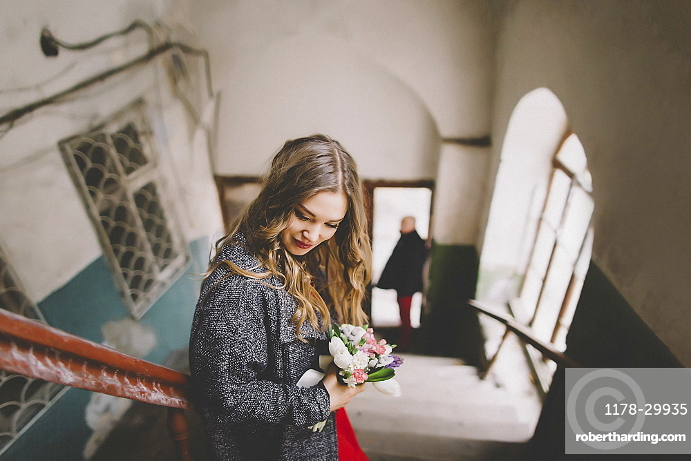 Bride standing on stairs while groom is waiting at entrance