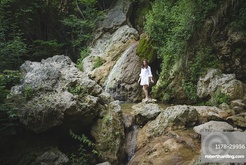 Ukraine, Crimea, Young woman walking barefoot on rocks in canyon