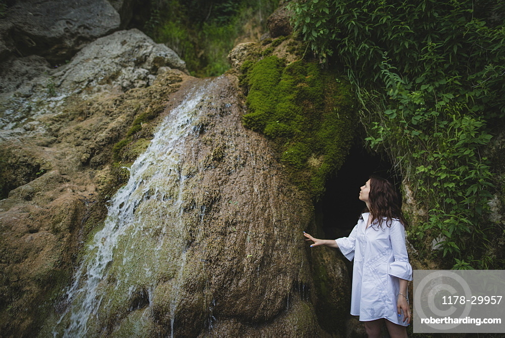 Ukraine, Crimea, Young woman standing by waterfall
