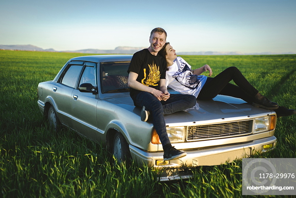 Ukraine, Crimea, Couple sitting on old fashioned car in rural scenery