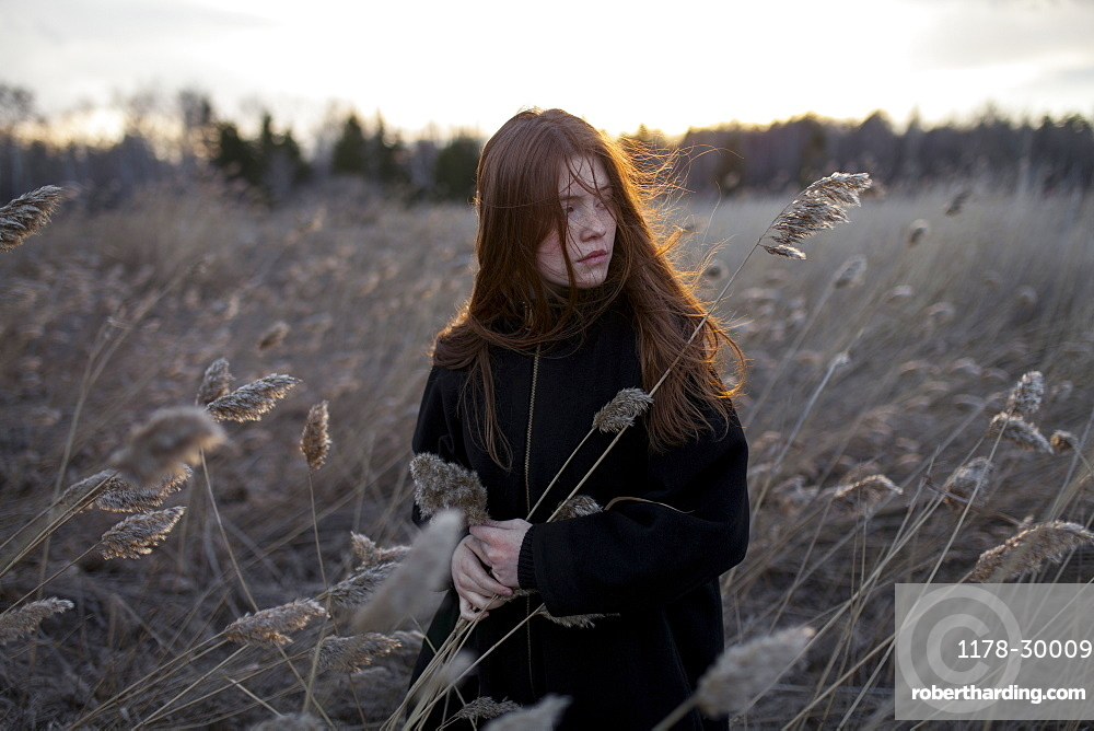Russia, Omsk, Portrait of teenage (16-17) girl in tall grass