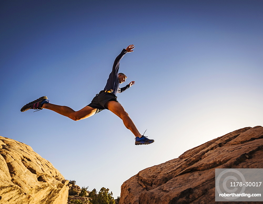 USA, Utah, St. George, Man jumping over rocks while running in landscape