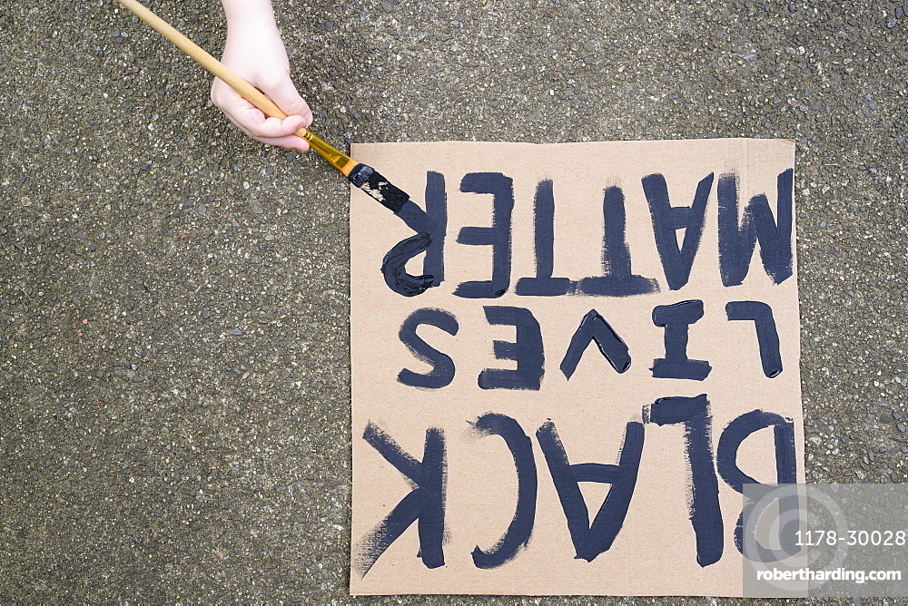 Woman's hand painting Black Lives Matter sign on cardboard