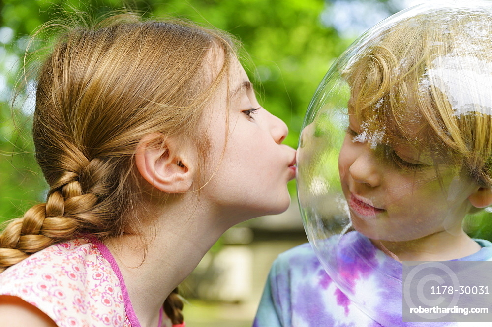 Girl kissing boy wearing bubble to socially distance