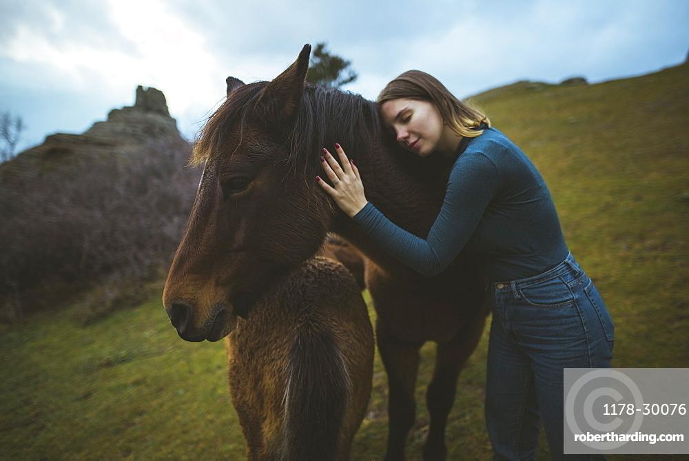 Ukraine, Crimea, Young woman embracing Icelandic horse