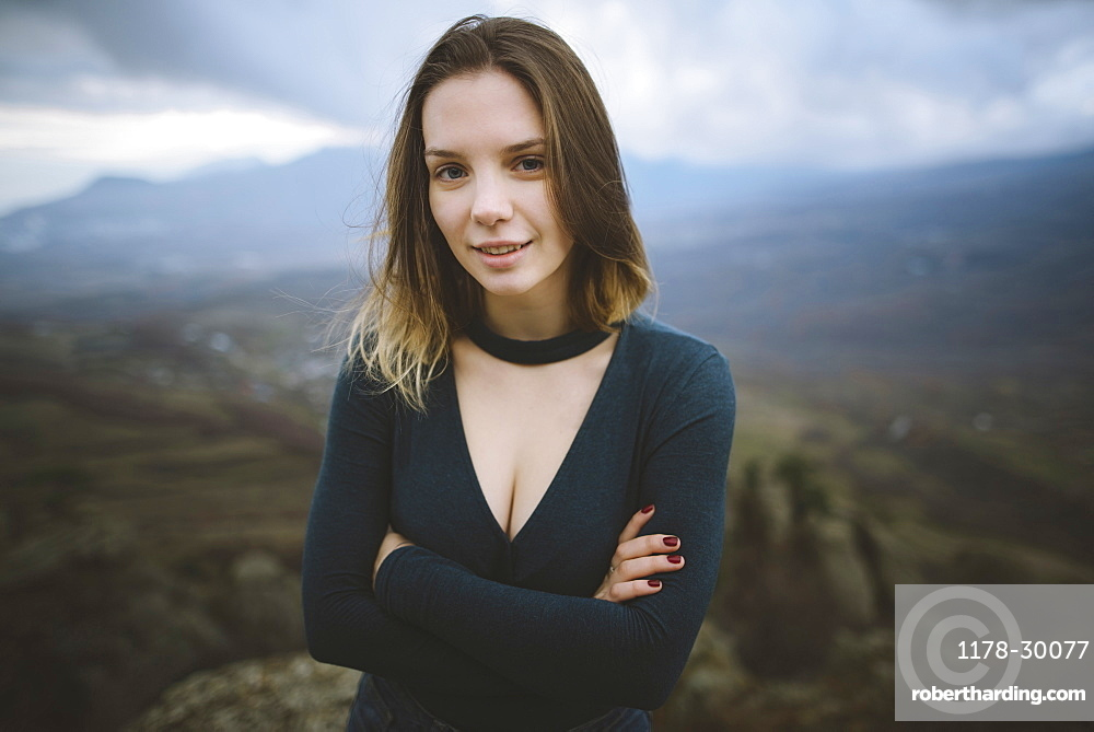 Ukraine, Crimea, Portrait of young woman with mountain valley in background