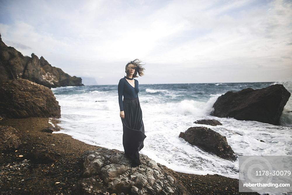 Ukraine, Crimea, Young woman standing on rocky beach
