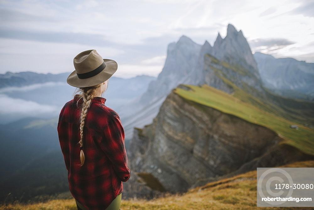Italy, Dolomite Alps, Seceda mountain, Woman looking at scenic view of Seceda mountain in Dolomites at sunrise