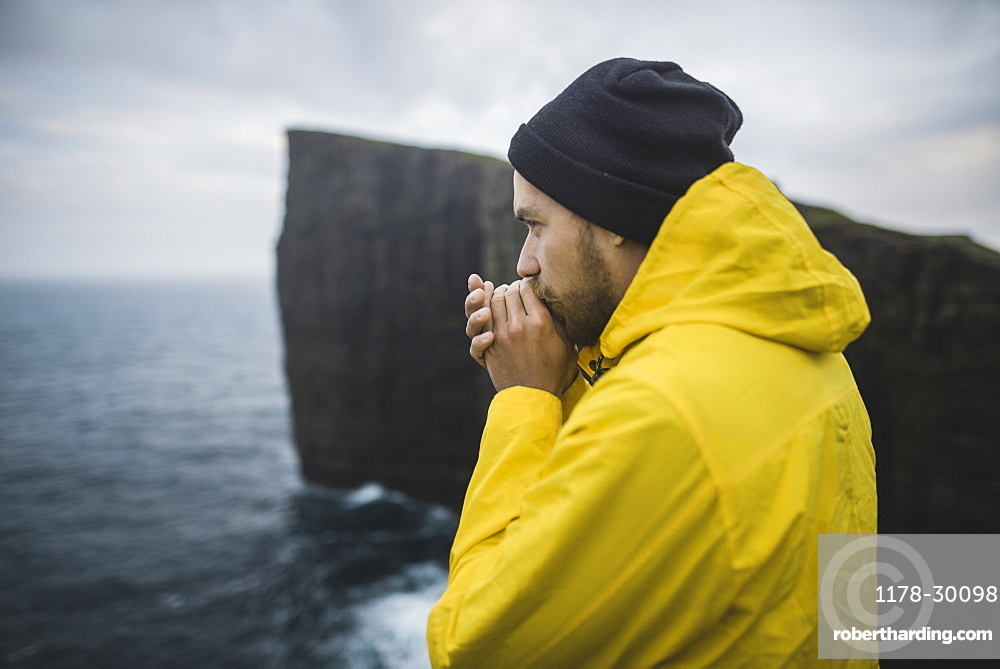 Denmark, Faroe Islands, Sorvagur, Man looking at sea coast with cliffs