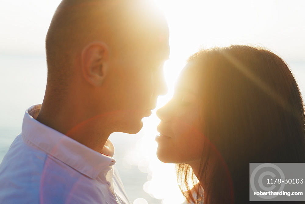 Couple face to face, backlit with sun rays