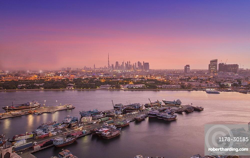 United Arab Emirates, Dubai, Boats on Dubai Creek and skyline at sunset