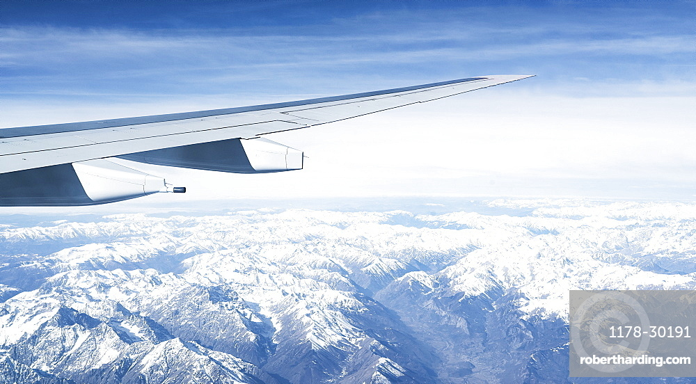 Switzerland, Canton Wallis, Airplane wing over snowy mountains