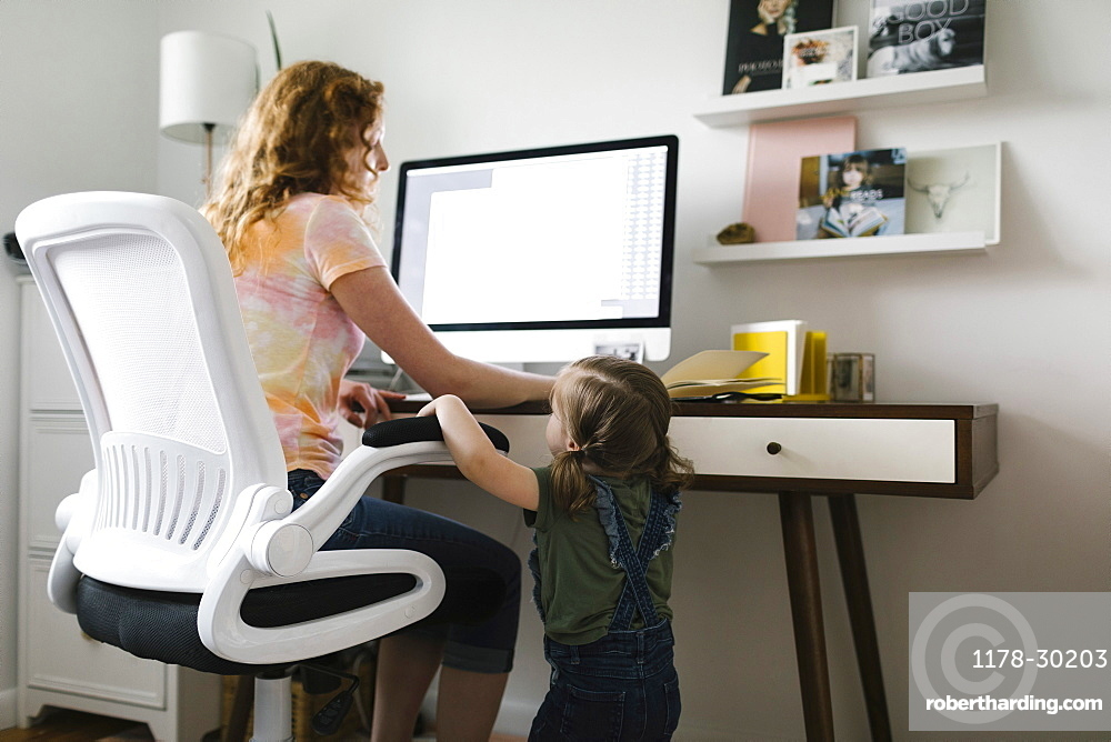 Girl (2-3) interrupting mother working from home