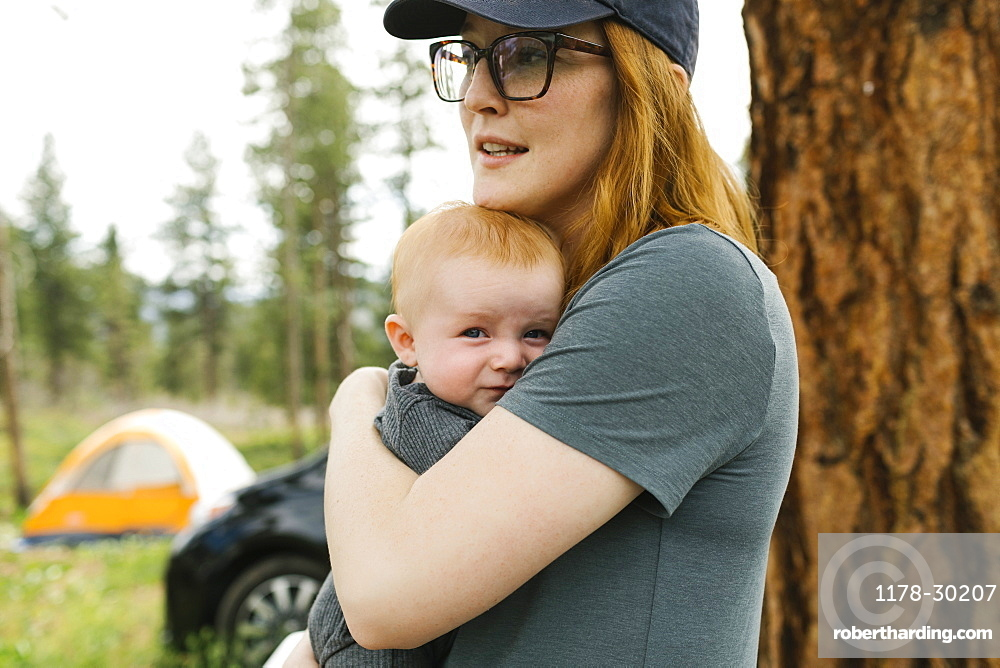 USA, Utah, Uninta Wasatch Cache National Forest, Woman holding baby son (6-11 months) during camping