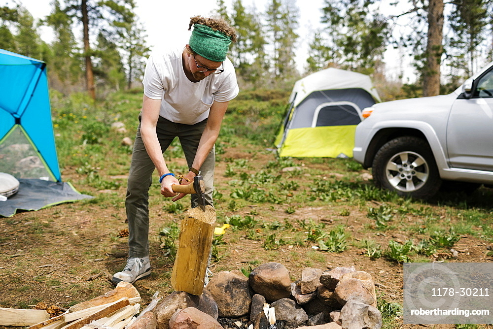 USA, Utah, Uninta Wasatch Cache National Forest, Man chopping wood during camping