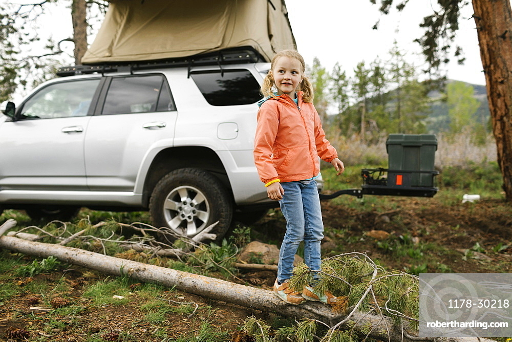 USA, Utah, Uninta Wasatch Cache National Forest, Girl (6-7) standing on log by car