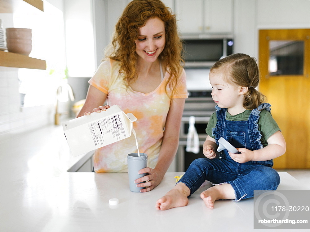 Mother pouring milk for daughter (2-3)