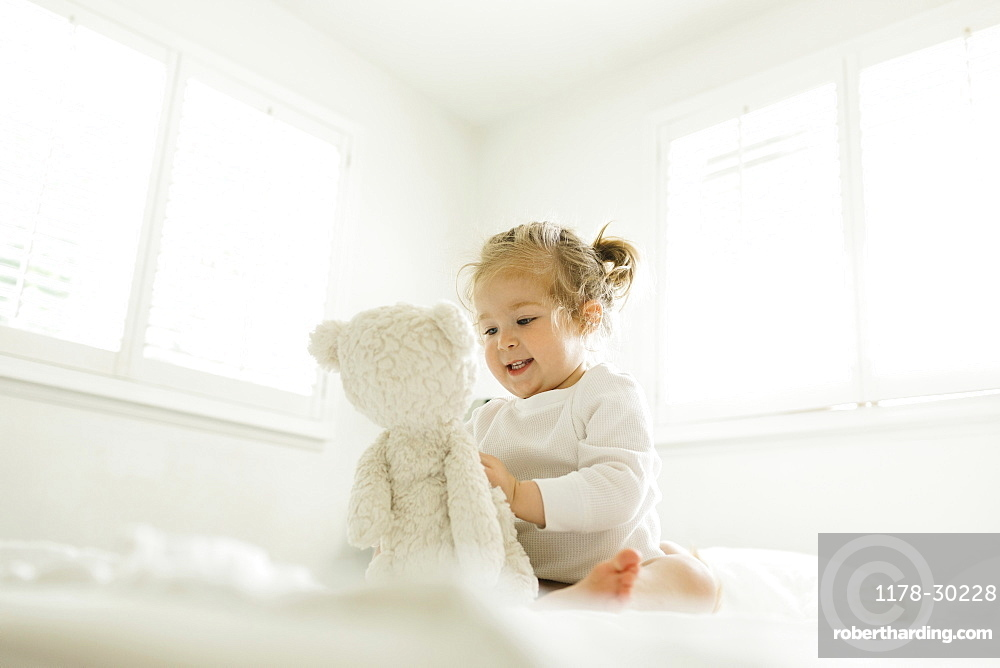 Toddler girl playing on bed with her teddy bear toy