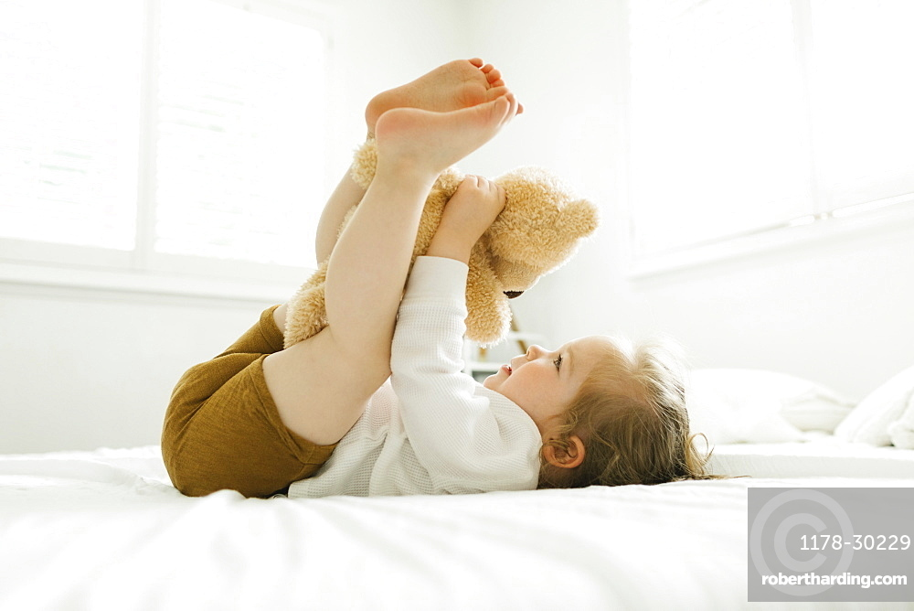 Toddler girl lying on bed with her teddy bear toy