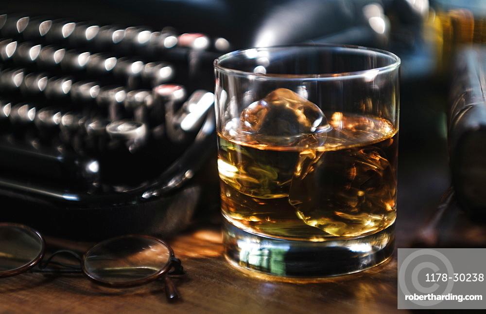 Whiskey glass next to typewriter on desk