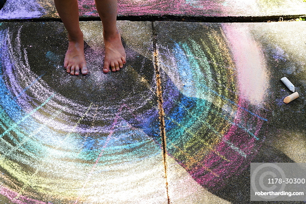 Low section of girl (6-7) standing on chalk drawing on pavement