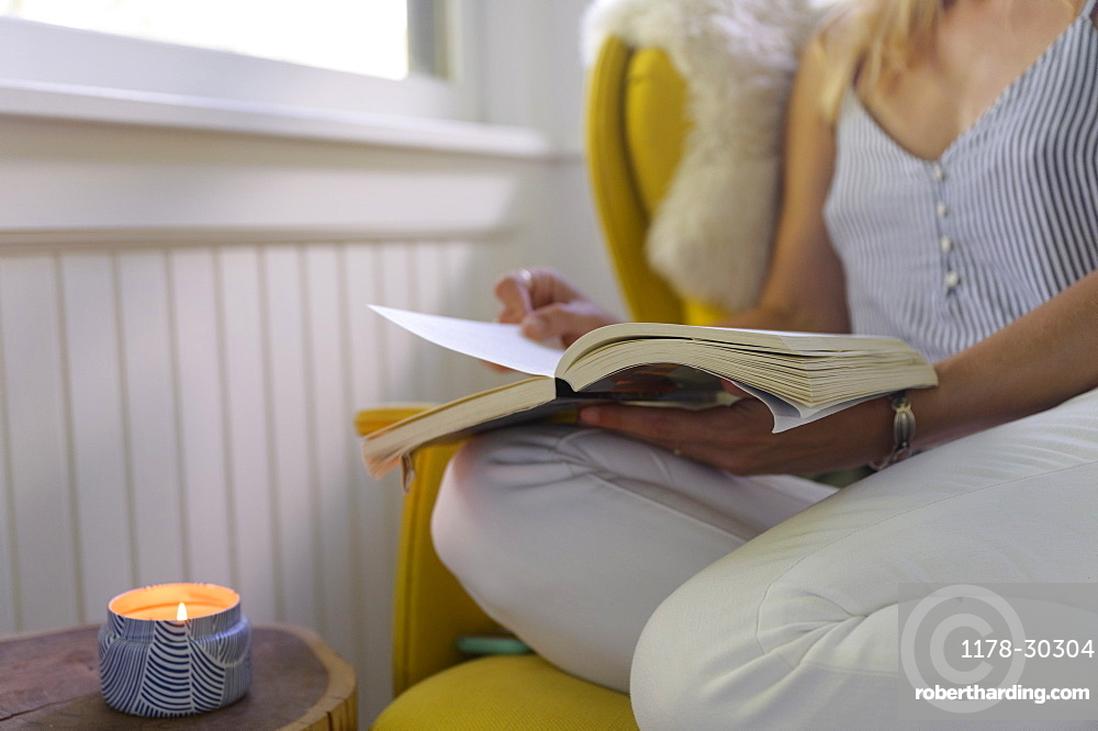 Midsection of woman reading book at home