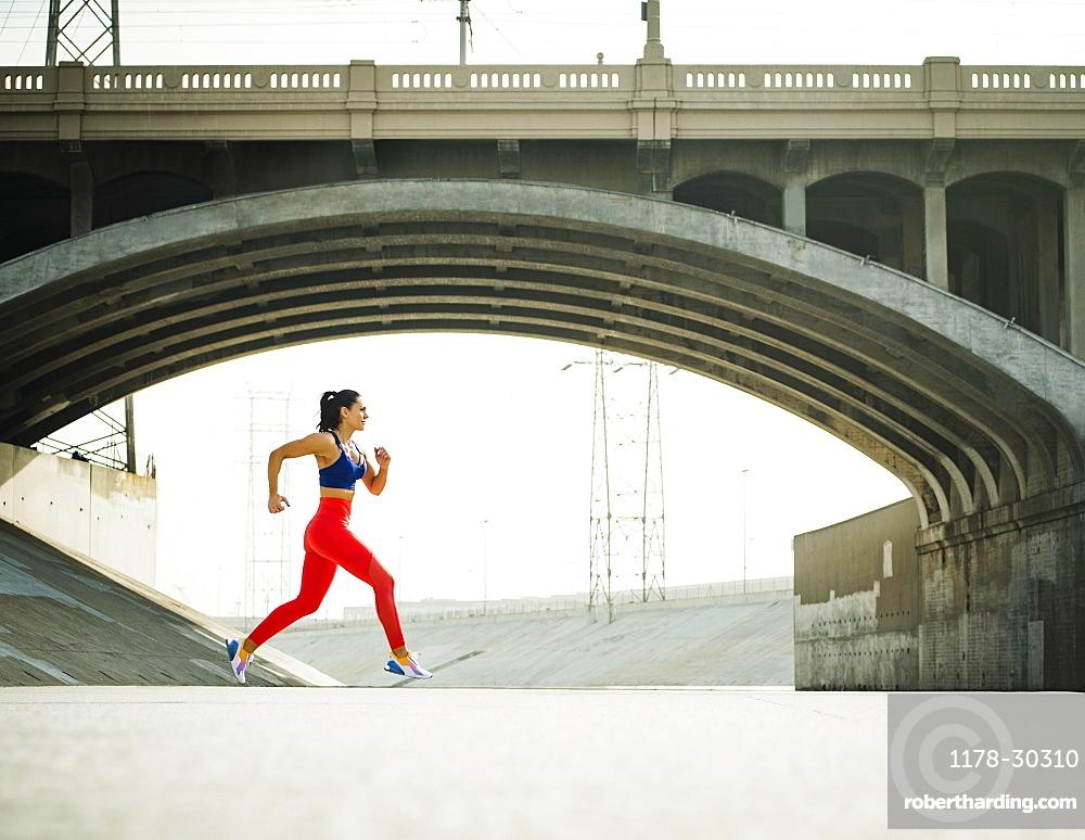 USA, California, Los Angeles, Sporty woman jogging in urban setting