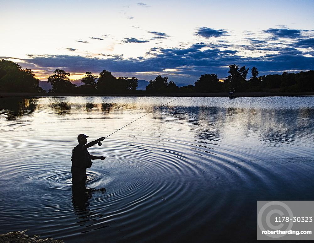USA, Utah, Salem, Silhouette of man fly fishing in lake at dusk