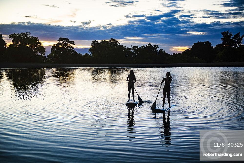 USA, Utah, Salem, Two teenage girls (14-15) on stand up paddle bards on lake at dusk