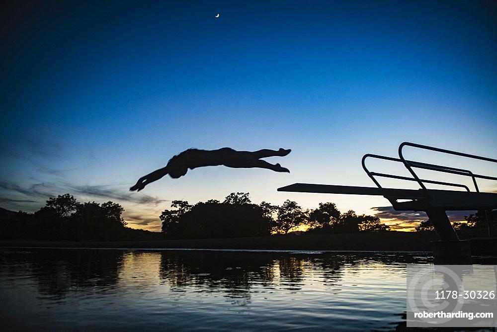 USA, Utah, Salem, Teenage girl (14-15) jumping from pier into lake at dusk