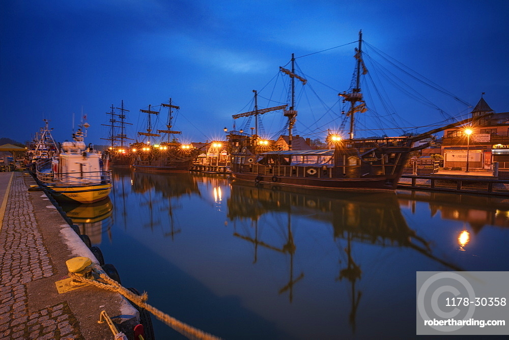 Poland, Pomerania, Leba, Historic tall ships moored at harbour at dusk