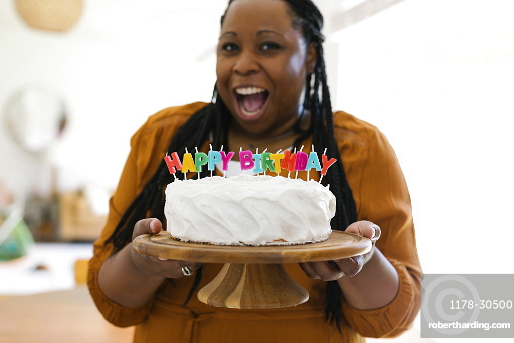 Portrait of smiling woman holding birthday cake with candles
