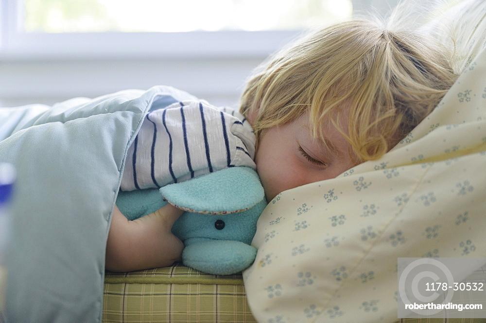 Boy (4-5) sleeping in bed